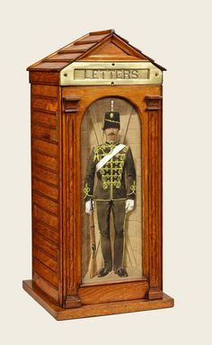 Photo #62 of #707070. An oak country house letter box, the door holding a watercolour of a guardsman by Richard Simkin.
