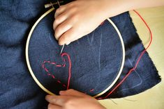 Otis hand sewing at How we Montessori red thread over traced hand Montessori Practical Life Sewing Activity