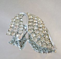 This #vintage rhinestone swoop brooch is just stunning!  It features a rhodium plated brooch with a swoop fold over shape filled with large clear rhinestones.  Rolling C-cla... #ecochic #etsy #jewelry #jewellery