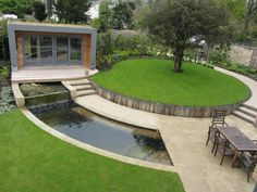 Strakke ronde tuin met gras vijver en waterval effect