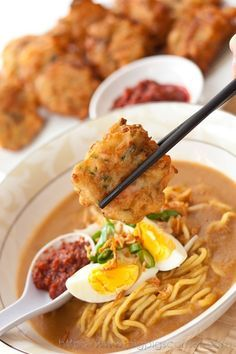 Mee Rebus recipe - It is yellow noodles served with a thick spicy potato-based gravy and garnished with a hard-boiled egg, spring onions, bean sprouts, fried shallots, tau kwa (dried/ fried beancurd) and lime juice. Malaysian Cuisine, Malaysian Food, Malaysian Recipes, Easy Delicious Recipes, Yummy Food, Mee Rebus, Prawn Fritters, Malay Food, Singapore Food