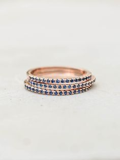 This eternity band ring set consists of three rose gold plated brass rings and blue Sapphire Cubic Zirconia diamonds set in a micro pave setting. Stones cover only half of the rings. These rings are very thin and dainty and are perfect for stacking - wear all three together or one one three different fingers for a more subtle look. For a single eternity band, click HERE