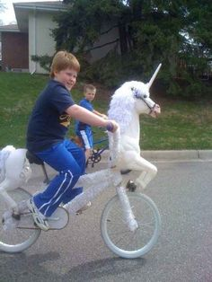 This kid, who is proudly riding a freakin' unicorn bike and it is glorious.