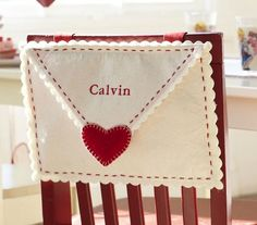 Cute made out of felt...Personalized Valentine Mailbox for Chair (Directions: Cut 2 rectangles & 1 triangle out of felt. Sew the base of the triangle to the base of 1 rectangle so they overlap to create a flap. Lift flap & place the other rectangle between the rectangle & triangle. Sew the 3 sides of the triangles together than are not covered by the triangle flap.)