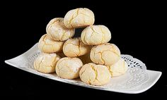 A photo of Amaretto Cookies stacked on a rectangular white dish lined with white doilies. (uses whole eggs instead of egg whites)