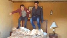 tyler posey and dylan o'brien jumping on a bed