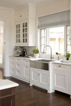 glass front cabinets, upper cabinets, blue roman shade, stainless steel apron sink, gooseneck faucet, white paint