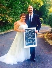 """Newlyweds Kelly and Jim show off their """"Surprise Wedding"""" sign at Greendance Winery."""