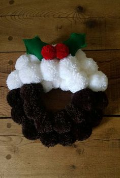 Fabulously tactile handmade Christmas wreath representing the delicious Christmas pudding!  The Christmas pompom wreath is approximately 11 inches in diameter and is felt backed with a ribbon ready for hanging. It is finished with handstitched holly leaves for authenticity! The wreath is packaged in a cake style box so it can be safely put away and used year after year.