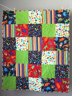 This modern baby boy quilt is completed and ready to ship to you! It features a cute, boy-friendly dinosaur theme in a bright primary color palette. This quilt is extra special because it is fully reversible with a large patchwork print on the back. Just flip it over for a new look! It would be perfect for the special little boy in your life and would be a beautiful addition to a dinosaur-themed nursery or toddlers room! What makes this item great: ♥ It is fully reversible! ♥ The striped…