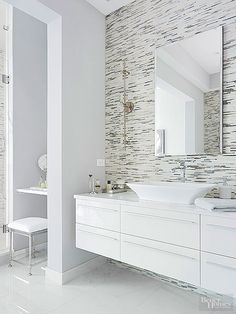 Horizontally+set+mosaic+tiles+and+sleekly+lined+floating+vanities+stylishly+enhance+the+perception+of+space+in+this+breezily+modern+bathroom+design.+Stepping+the+inner+doorway+back+from+the+shower+created+space+for+a+dressing+table.