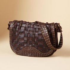 """Compactly sized, full of substance and character, this rugged bag from Frye® is supple dark brown vintage leather, well-embellished with a studded woven flap and shoulder strap covered in hammered studs. Magnetic closure, striped fabric lining, two section interior with one zip and two open pockets. Imported. 11""""W x 4""""D x 8""""H.View our entire Frye Collection."""