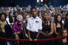 A young boy listens to Barack Obama speak at the Congressional Black Caucus Foundation conference