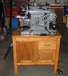 Ammco Metal Shaper.  This small unit was designed to do yeoman's service in the small shop.  These are mesmerizing to watch in action.  The wooden cabinet on this one was created along the pattern of the originals, which were designed to keep the machine portable and its tooling handy to the user.