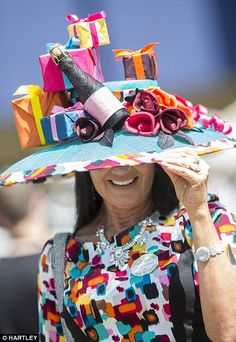 Enjoying the day: A racegoer arrives in a fabulous birthday themed hat, complete with a mini bottle of champagne