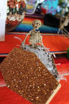 Sparkly coffin with skeleton for Dia de los Muertos altar by Ben White Florist.