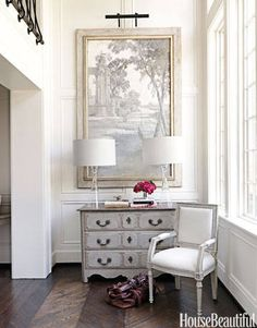 The entry's framed wallpaper fragment and antique French chest establish the neutral palette