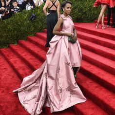 Kerry Washington in PRADA at the 2015 Metropolitan Museum of Art's Costume Institute Gala.  Kerry Washington wore a PRADA clove pink silk faille open back gown with bow accented shoulders.  The full skirt is hand-stitched with grosgrain ribbon and crystal embroidery in a floral motif and lined with grey taffeta enriched with a geometric pattern of crystal, plexi and stones. She complemented the look with kelly green silk satin pumps and a hard case emerald green silk satin clutch…