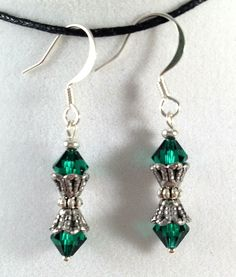 Dainty crystals with silver bead cap accents. Rich emerald green tone Swarovski crystal dangles.