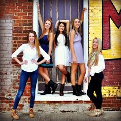 Large group photos for friends. group of 5 girls pose in front of old door.