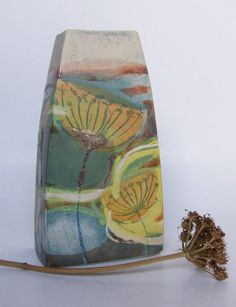 Small Stoneware vase decorated in blue and gold wild flower motif.