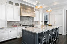 1006 Navy Counter Stools sit on dark wood floors in front of a gray kitchen island painted in Benjamin Moore Gunmetal and accented with a fitted with an undermount sink and a gold vintage deck mount faucet illuminated by two The Urban Electric Co Globus lights.