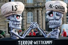 A carnival float labeled 'Terror Competition' shows skeletons in turbans, representing IS and Al Qaeda, arm-wrestling at the traditional Rose Monday carnival parade in Duesseldorf, Germany, Monday