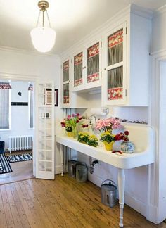 Cabinets and a massive double-drainboard sink dating to the 1920s are the focal point of the pantry in a 1799 farmhouse restored in Colonial Revival style.