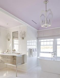 Calming purple and white contemporary bathroom boasts a freestanding tub placed…
