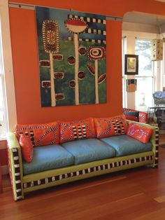 Love the pattern painted on the sofa...and the salmon coral back cushions mixed with blue seat cushions. The black and white on the lime apple green on the sofa- Magnificent. Flowers and painted sofa by helvismith