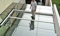 O profissional da Digicom Coberturas caminha sobre a cobertura de vidro com toda segurança.