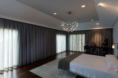 Dark gray curtains stretch all across the wall on two sides of this master bedroom offering ultimate privacy and a softening touch. Overhead, a delicate chandelier mimics a cluster of stars.