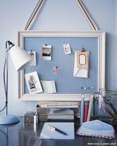 """""""A hardworking bulletin board is, quite literally, pretty as a picture when covered with cheerful fabric, placed in a frame, and hung from a wide ribbon. The frame is painted to complement the fabric, which makes a perfect background for favorite photographs and letters, along with the more prosaic matters of life such as the phone bill and the grocery list."""""""