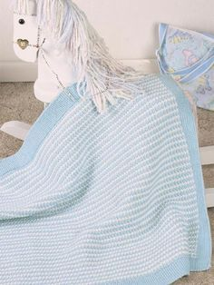 The Warm & Cuddly Baby Afghan keeps baby swaddled in comfort.  Create this and other baby gifts and accessories with free baby knitting patterns from Freepatterns.com.