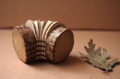Libretita hecha con rodajas de ramas (restos de podas o ramas caídas). Funciona muy bien como elemento decorativo o libro objeto. Encuadernación copta artesanal. Ideal para hacer un regalo único y diferente. Va acompañada de una bolsa de tela de color marrón oscuro. 100% hecho a mano.