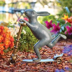 """This bunny garden statue is hoppy to share her upbeat attitude. She gleeful """"scoots"""" through your garden, balancing on 1 leg on her bronze scooter. Made of aluminum with a hand-painted finish in verdigris and bronze with highlights, this garden sculpture comes with 2 spikes to securely place it in the ground. She is sure to be a standout among your other plants, flowers, and yard art."""
