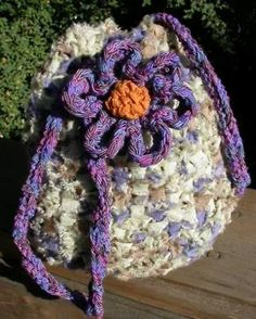 Drawstring bag with crocheted flower and ribbon strap.