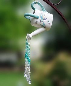 Watering can sun catcher with light blue and sparkling glass, acrylic and crystal beads pouring for the spout.
