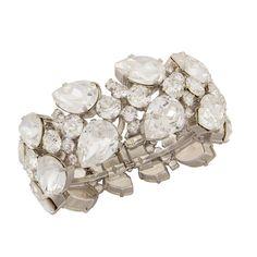 Ganz im puristischen Design gehalten ist die Armspange Glowy aus versilbertem Messing mit weißen Swarovski-Steinen gefertigt. Ein dezentes Statement-Sc…