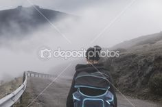 Women traveling with backpack on the road through dense fog