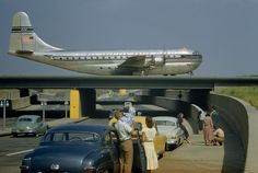 Sightseers park to watch a Stratocruiser taxi across an underpass in Queens, New…