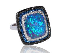 Bassali's cocktail ring is dark and stormy, with seemingly mystical powers. The center entrances with a triplet opal center in glowing shades of blue and green. The dark part comes from the moody jet-black diamonds and sapphires that make up two-thirds of the three-row frame, which also includes an inner rim of diamonds. The whole look is set in 14k white gold with a smooth band.