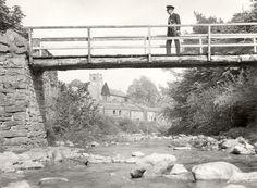 Postman crossing stream on wooden bridge, Muker, Yorkshire, 1930s. (POST 118/1237)