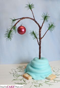 It's Charlie Brown's Christmas Tree as a CAKE! Learn how to make this adorable scraggly tree sweetly wrapped in Linus' blue blanket complete with an edible red chocolate ornament! Free step by step photo tutorial! Merry Peanuts Christmas!