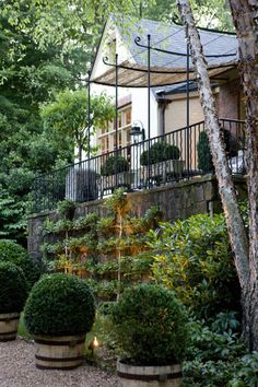 upper stone-retained terrace with interesting iron awning structure, fence w/alternating wavy pickets and faux bois planters.  Lower crushed-stone patio w/whiskey barrel planters and espalier. by architect Bill Litchfield / MIKE HAMMERSMITH builders (photo by Rob Brinson), Atlanta, GA