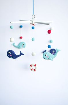 Splish splash! This whale baby mobile will create a harmonious atmosphere in your baby's nursery while also promoting hand-eye development. Designed in meticulous detail, it features hand-felted whales swimming alongside bright felt balls with a red lifebuoy to complete the design.