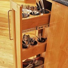 make use of a narrow vertical space. love this idea instead of a drawer. you can pop the cups in the dishwasher, unlike an awkward utensil tray.