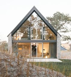 This holiday home situated by the dunes of the Wadden Sea on the Eiderstedt peninsula blends in perfectly with its surroundings: The colours of the beach can be found in the stone façade, in the slate-gray wooden wind.