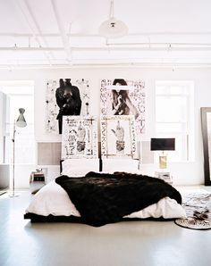 Black and white bedroom with large artwork behind the bed.