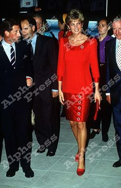Diana wearing a scarlet silk tunic top paired a w/ tiered satin skirt by Tomasz Starewski w/colored glass buttons. The colour corresponds to that used for the lining of a toreador's cape.